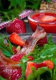 Ensalada útil de la fresa con el arugula, las nueces y el tocino, salsa de la baya Foto de archivo