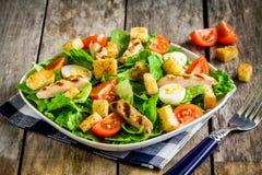 Ensalada César con el pollo, los cuscurrones, los huevos de codornices y los tomates de cereza asados a la parrilla Foto de archivo libre de regalías
