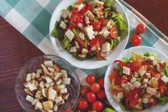 Ensalada César con los cuscurrones, preparación, pollo, tomates de cereza Imagenes de archivo