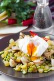 Ensalada caliente con las patatas, jamón, guisantes, setas, huevo escalfado Fotografía de archivo