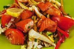 Ensalada caliente con los salmones y las verduras en una placa Foto de archivo libre de regalías