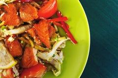 Ensalada caliente con los salmones y las verduras en una placa Foto de archivo