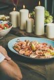 Ensalada, camarones y velas en la tabla de madera Fotos de archivo libres de regalías