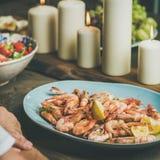 Ensalada, camarones y velas en la tabla de madera, cosecha cuadrada Fotos de archivo libres de regalías