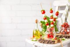 Ensalada clásica de los Canapes de Caprese del italiano con los tomates, la mozzarella y la albahaca fresca imagen de archivo libre de regalías