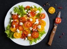 Ensalada colorida, hojas frescas y tomates de cereza rojos y amarillos cortados, placa blanca, cuchillo, fondo de piedra negro, v Fotos de archivo libres de regalías