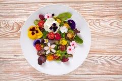 Ensalada comestible de las flores en una placa imagenes de archivo