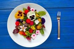 Ensalada comestible de las flores en una placa foto de archivo