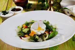 Ensalada con el huevo escalfado, pepinos, arugula, col, pimientas, aún vida en una comida bonita de la tabla de la pizarra de mad Foto de archivo