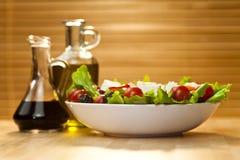 Ensalada con la preparación del aceite de oliva y del vinagre balsámico Imágenes de archivo libres de regalías