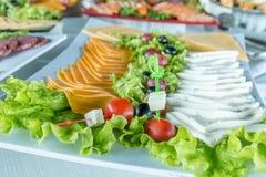 Ensalada con la salchicha, verdes y otro en la tabla con la tabla blanca Concepto del abastecimiento Fotografía de archivo