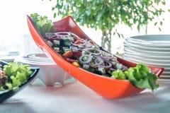 Ensalada con la salchicha, verdes y otro en la tabla con la tabla blanca Concepto del abastecimiento Imagenes de archivo