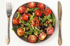 Ensalada con las berenjenas y los tomates de cereza en una placa oscura en un fondo blanco, visión superior imagen de archivo libre de regalías
