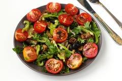 Ensalada con las berenjenas y los tomates de cereza en una placa oscura en un fondo blanco, visión superior fotografía de archivo