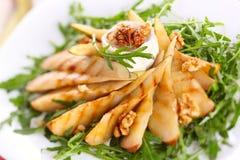Ensalada con las peras, las nueces y el queso de cabra asados Imagen de archivo