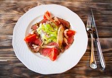 Ensalada con las rebanadas de carne ahumada y de verduras en una placa blanca Fotografía de archivo libre de regalías