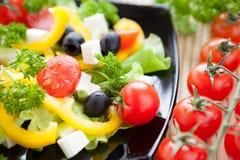 Ensalada con las verduras frescas en una placa negra imagen de archivo libre de regalías