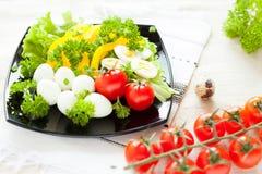 Ensalada con las verduras frescas y los huevos de codornices en una placa cuadrada fotos de archivo libres de regalías