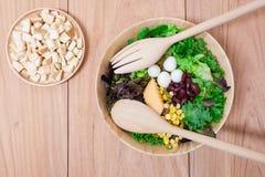 Ensalada con los huevos, el cantalupo, la nuez del pan y la verdura verde en placa de madera Imágenes de archivo libres de regalías