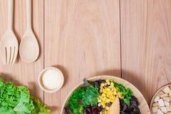 Ensalada con los huevos, el cantalupo, la nuez del pan y la verdura verde en placa de madera Foto de archivo