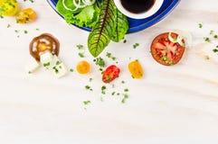 Ensalada con los tomates, el queso feta y el vinagre balsámico en placa azul en el fondo de madera blanco, visión superior Imagen de archivo libre de regalías