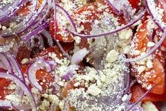 Ensalada con los tomates frescos, la cebolla roja y el queso feta rallado Fotografía de archivo