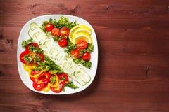 Ensalada con los tomates, los pepinos, las pimientas dulces y las cebollas en una placa cuadrada en una tabla de madera Foto de archivo libre de regalías