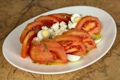 Ensalada con los tomates pelados en una placa blanca en un fondo de madera imagen de archivo libre de regalías