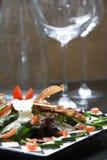 Ensalada con los vidrios de vino en el fondo Foto de archivo libre de regalías