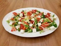 Ensalada con tomates, una mano y un queso Feta imagenes de archivo