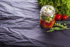 Ensalada con verdes en el pote en un tablero de madera, fondo texturizado negro de las verduras frescas Con el espacio para el te imagenes de archivo