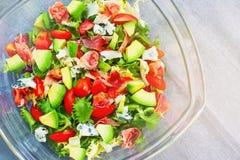 Ensalada con verdes mezclados frescos, el aguacate, los tomates de cereza, el jamón y el queso del Roquefort Foto de archivo