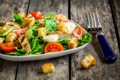 Ensalada César con los cuscurrones, los huevos de codornices, los tomates de cereza y el pollo asado a la parrilla Foto de archivo libre de regalías