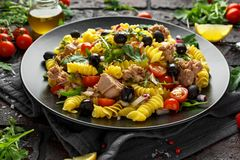Ensalada de atún de las pastas con los tomates, el cohete salvaje, las aceitunas negras y la cebolla roja imagen de archivo