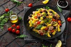 Ensalada de atún de las pastas con los tomates, el cohete salvaje, las aceitunas negras y la cebolla roja imagenes de archivo
