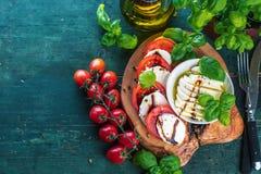 Ensalada de Caprese El queso de la mozzarella, los tomates y la hierba de la albahaca se va imagen de archivo