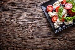 Ensalada de Caprese Ensalada mediterránea Albahaca de los tomates de cereza de la mozzarella y aceite de oliva en la tabla de rob Imagenes de archivo