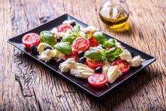 Ensalada de Caprese Ensalada mediterránea Albahaca de los tomates de cereza de la mozzarella y aceite de oliva en la tabla de rob Foto de archivo libre de regalías
