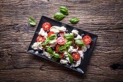 Ensalada de Caprese Ensalada mediterránea Albahaca de los tomates de cereza de la mozzarella y aceite de oliva en la tabla de rob Imagen de archivo libre de regalías