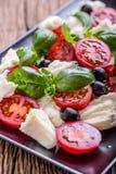 Ensalada de Caprese Ensalada mediterránea Albahaca de los tomates de cereza de la mozzarella y aceite de oliva en la tabla de rob Fotografía de archivo libre de regalías
