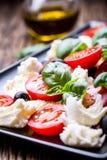 Ensalada de Caprese Ensalada mediterránea Albahaca de los tomates de cereza de la mozzarella y aceite de oliva en la tabla de rob Foto de archivo