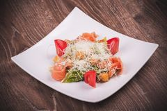 Ensalada de Cesar con los salmones, el tomate, los cuscurrones y el queso Foto de archivo