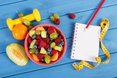 Ensalada de fruta, cinta métrica con pesas de gimnasia y la libreta para escribir notas, forma de vida sana y concepto de la nutr Fotos de archivo