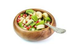 Ensalada de fruta con el plátano, el kiwi y la granada en un cuenco de madera, Imagenes de archivo