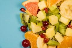 Ensalada de fruta fresca con la fruta cítrica en un fondo azul con un lugar para la inscripción Ensalada fresca de la fruta cítri Foto de archivo