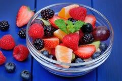 Ensalada de frutas deliciosa en un cuenco en la tabla foto de archivo