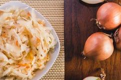 Ensalada de la chucrut y de zanahorias en una placa blanca y varios bulbos de la cebolla en una tabla de madera fotografía de archivo