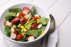 Ensalada de la espinaca con los tomates y el maíz de cereza en el cuenco, tabla de madera blanca Imagen de archivo