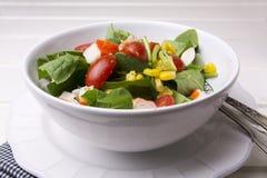 Ensalada de la espinaca con los tomates y el maíz de cereza en el cuenco, tabla de madera blanca Foto de archivo