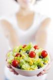 Ensalada de la mujer joven y de la verdura aislada en blanco Foto de archivo